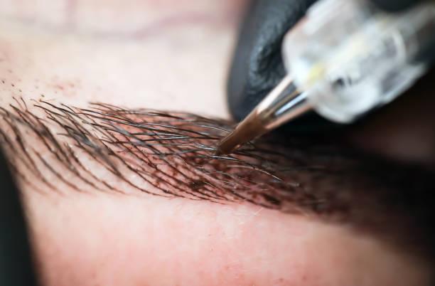 microblading eyebrows, getting facial care and tattoo at beauty salon - durabilidade imagens e fotografias de stock