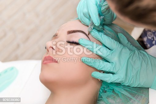 istock Microblading eyebrows work flow in a beauty salon. Woman having her eye brows tinted. Semi-permanent makeup for eyebrows. Focus on model's face and eyebrow 929239380