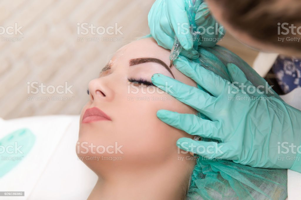 Microblading eyebrows work flow in a beauty salon. Woman having her eye brows tinted. Semi-permanent makeup for eyebrows. Focus on model's face and eyebrow – zdjęcie