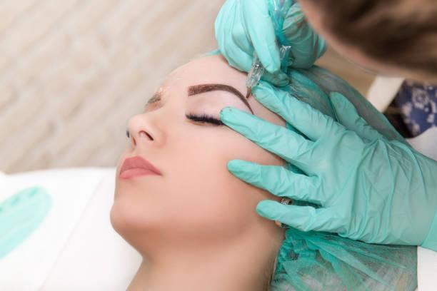 Microblading sourcils des flux de travail dans un salon de beauté. Femme ayant ses sourcils teintés. Maquillage semi permanent pour sourcils. Se concentrer sur le visage et les sourcils du modèle - Photo