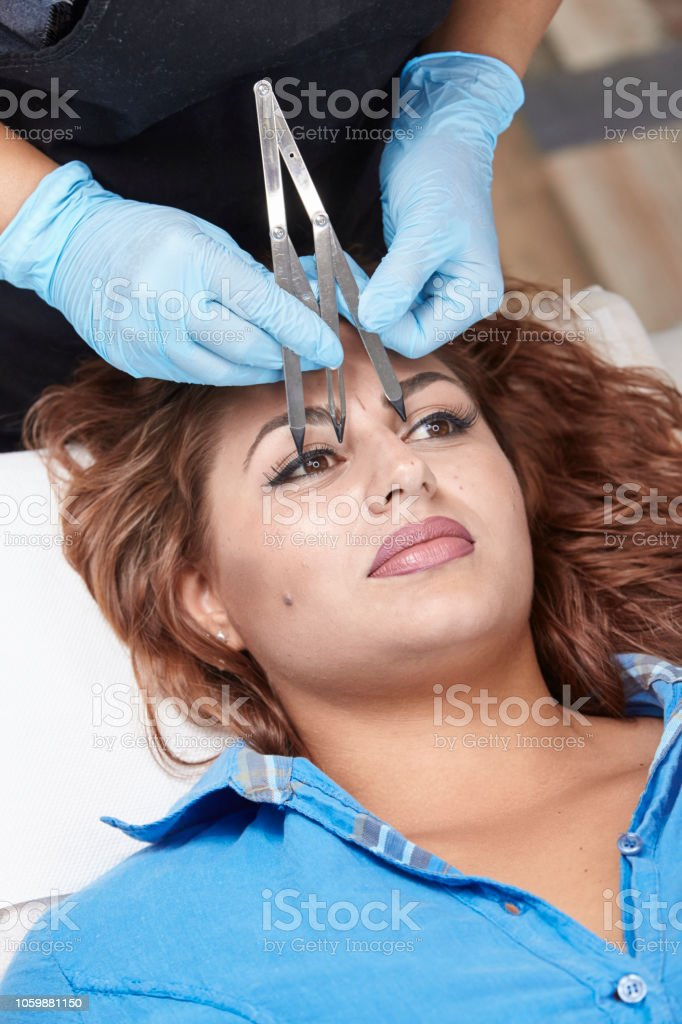 microblading, woman checking  eyebrow shape with caliper. elevated view. stock photo
