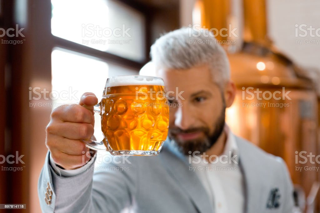 Microbrewery owner checking quality of beer Microbrewery owner checking quality of beer. Focus on beer mug. Adult Stock Photo