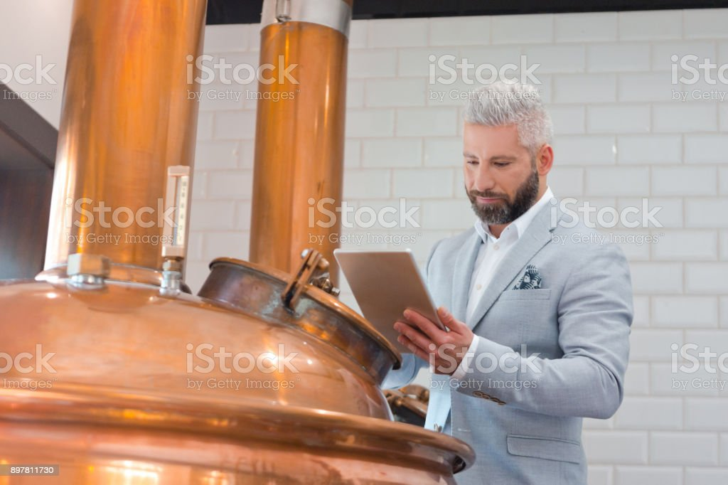 Microbrewery owner using a digital tablet in fermenting section Mature businessman with digital tablet standing by a copper vat in brewery. Micro brewery owner with a digital tablet in fermenting section of beer manufacturing factory. Adult Stock Photo
