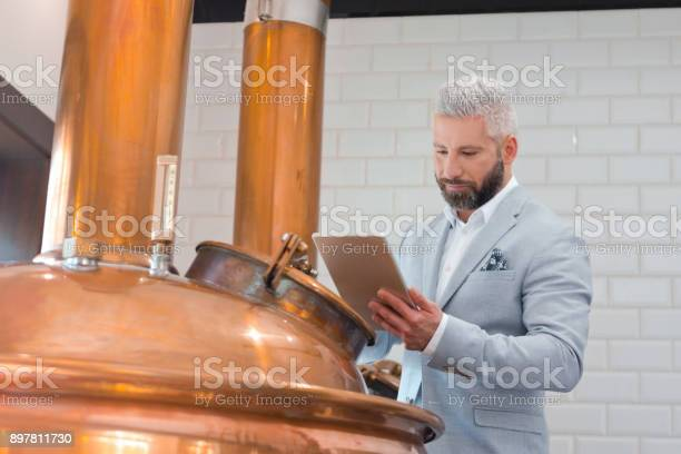 Microbrewery Owner Using A Digital Tablet In Fermenting Section Stock Photo - Download Image Now