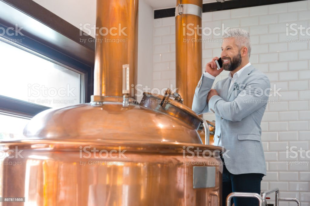 Microbrewery owner using a mobile phone Mature businessman standing by a copper vat in brewery talking on mobile phone. Micro brewery owner using cell phone in fermenting section of beer manufacturing factory. Adult Stock Photo