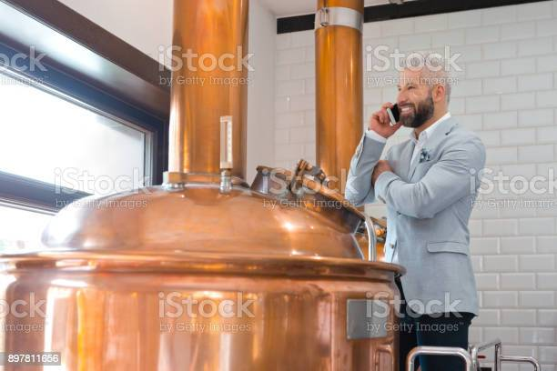 Microbrewery Owner Using A Mobile Phone Stock Photo - Download Image Now