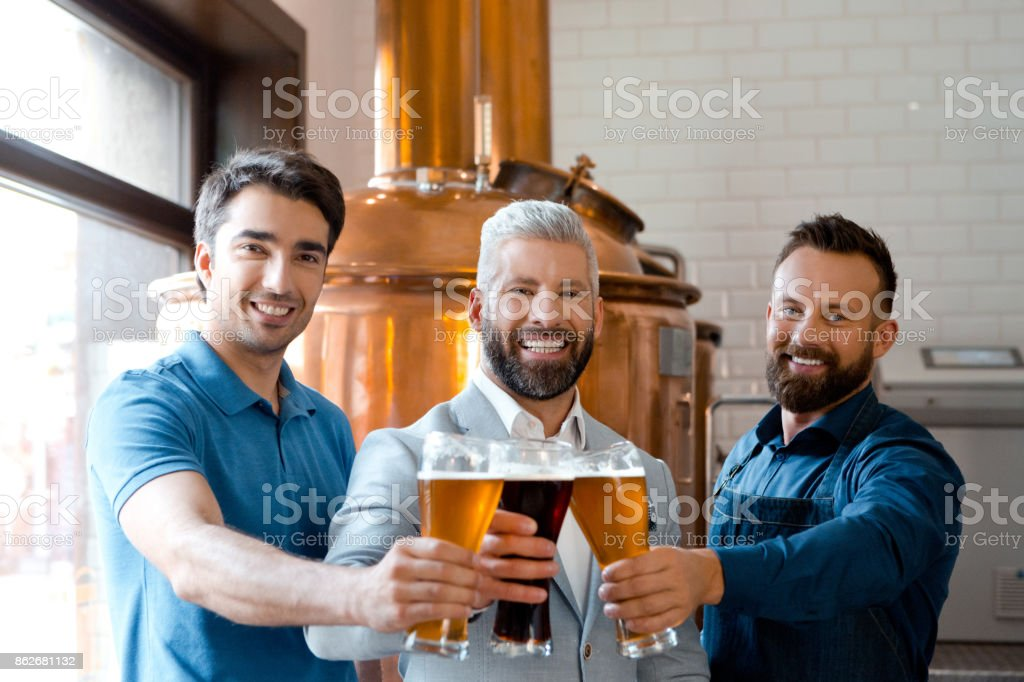 Microbrewery team toasting with beer Owner, brewer master and bartender toasting with beer glasses in microbrewery, smiling at the camera. Adult Stock Photo