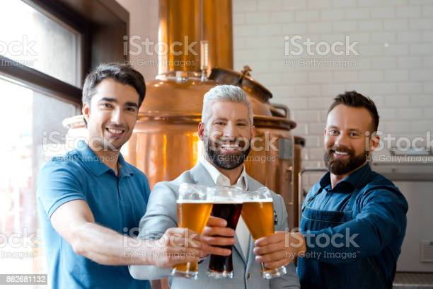 Microbrewery Team Toasting With Beer Stock Photo - Download Image Now