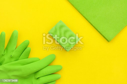 istock Microfiber and green sponge, kitchen latex gloves on a yellow background, top view. 1262973456