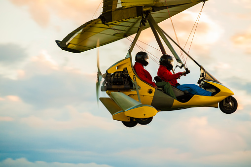 Microlight aircraft in the air flying in sunset