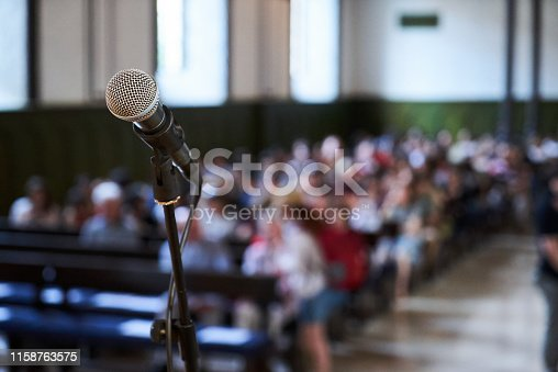 478810450 istock photo Microphone and abstract blurred conference hall or seminar room background 1158763575
