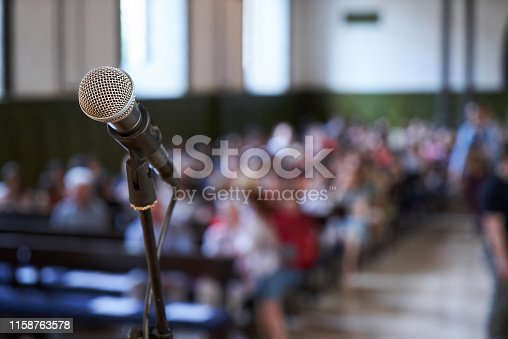 478810450 istock photo Microphone and abstract blurred conference hall or seminar room background 1158763578