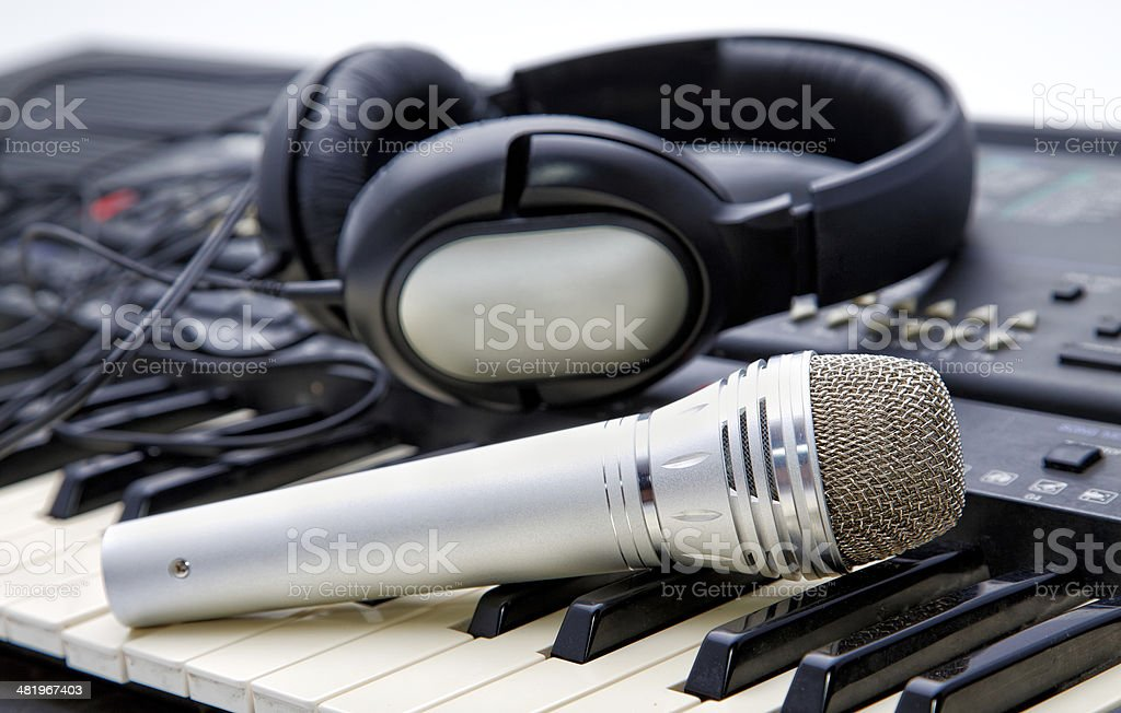 microphone and ear-phones lie on the keyboard royalty-free stock photo