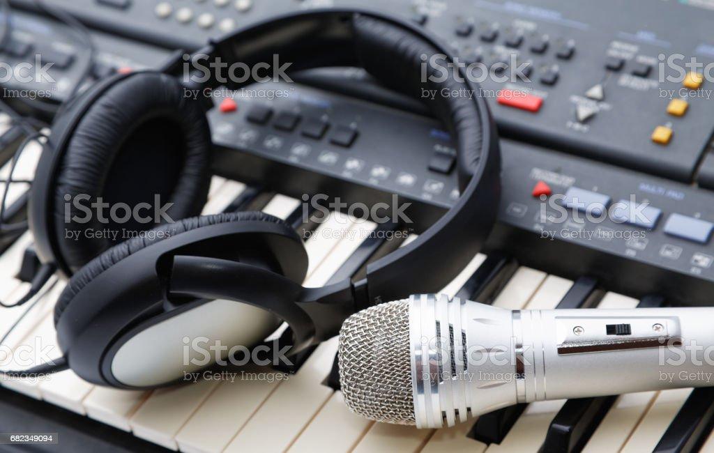 microphone and ear-phones lie on the keyboard zbiór zdjęć royalty-free