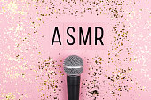 istock A microphone and letters ASMR on pink background. Minimal compostion. 1264462844