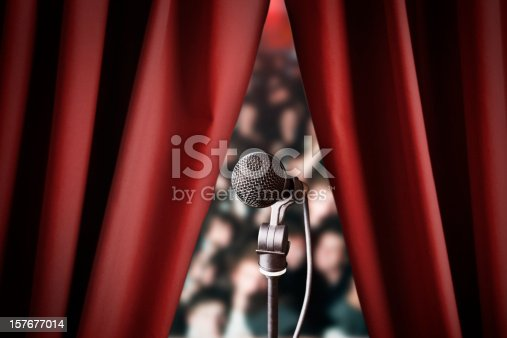 istock Microphone and out of focus audience through red drapes 157677014
