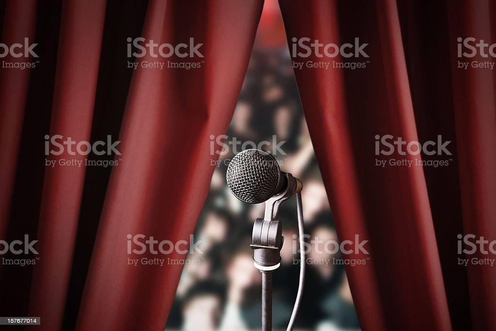 Microphone and out of focus audience through red drapes stock photo