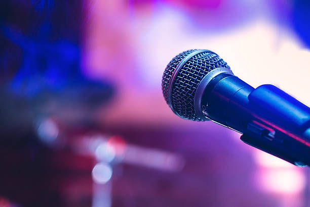 Microphone at concert Microphone on the stage on violet background. singer stock pictures, royalty-free photos & images