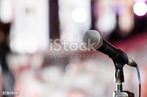 istock Microphone close-up. Focus on mic. Abstract blurred conference hall or wedding banquet on background. Event concept 913616132