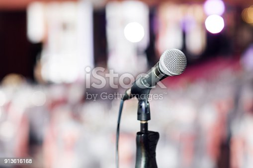 671733994 istock photo Microphone close-up. Focus on mic. Abstract blurred conference hall or wedding banquet on background. Event concept 913616168