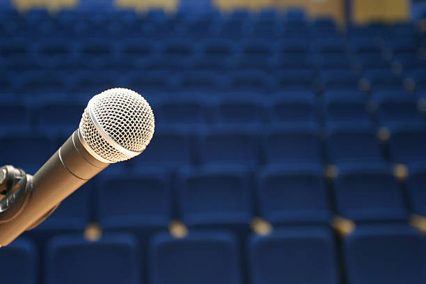 microphone closeup on empty conference hall stock photo