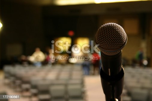 A lone microphone on stage as the auditorium begins to fill.