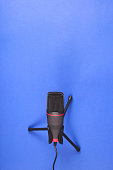 istock Microphone for recording sound and podcasts on blue. 1202818561