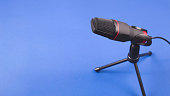 istock Microphone for recording sound and podcasts on blue. 1202818566