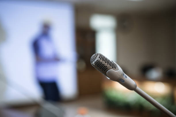 Microphone for speech on abstract blurred conference hall Microphone for speech on abstract blurred conference hall  Prepare for speaker on stage in seminar desk room background, Business meeting and education in teaching classroom concept spokesperson stock pictures, royalty-free photos & images