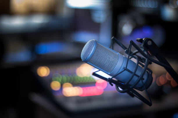 Microphone in a professional recording or radio studio, equipment in the blurry background stock photo