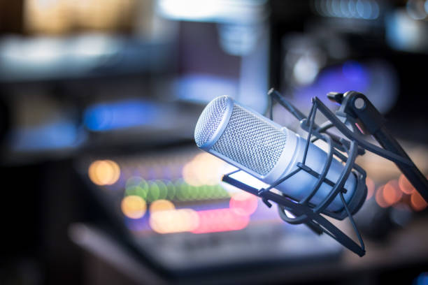 Microphone in a professional recording or radio studio, equipment in the blurry background Professional studio microphone, recording studio, equipment in the blurry background performing arts event stock pictures, royalty-free photos & images
