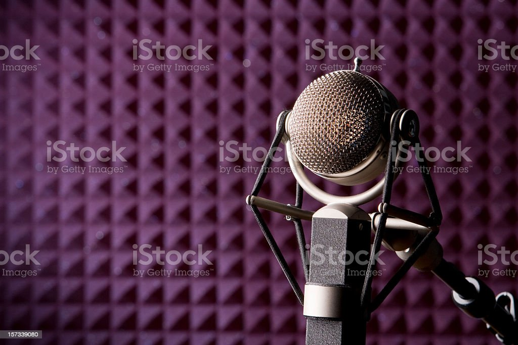 A microphone in a purple recording studio royalty-free stock photo