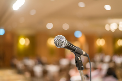 istock microphone in concert hall or conference room lights background 525142399