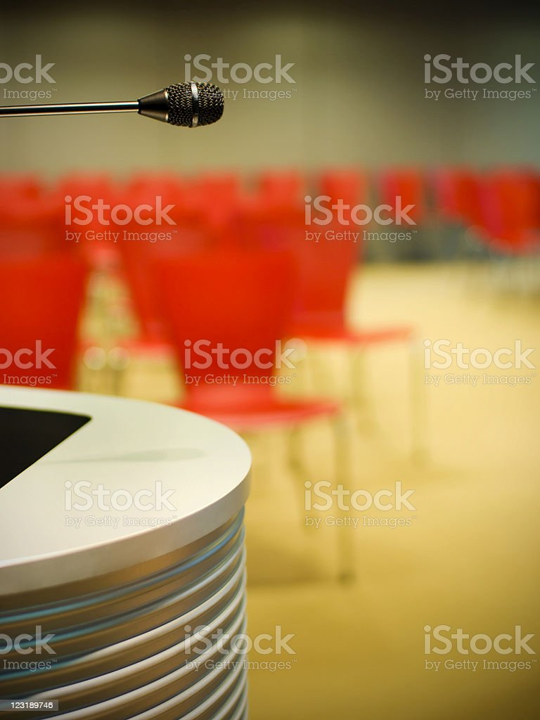 Microphone in empty seminar room with red chairs royalty-free stock photo