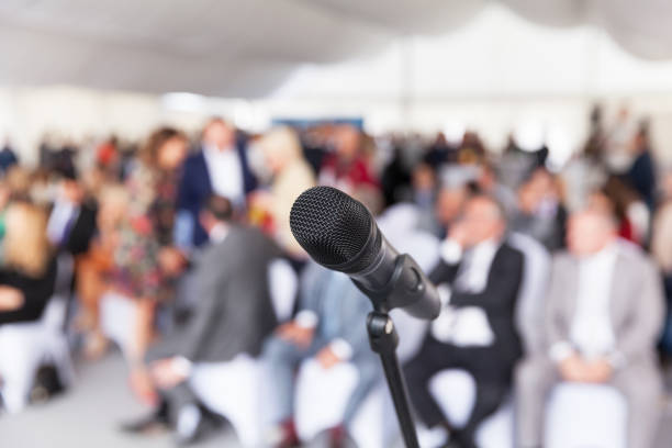 Microphone in focus against blurred audience. Participants at the business or professional conference. stock photo