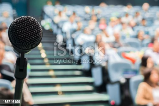 491577806 istock photo Microphone in Focus Against Blurred Audience 186746159
