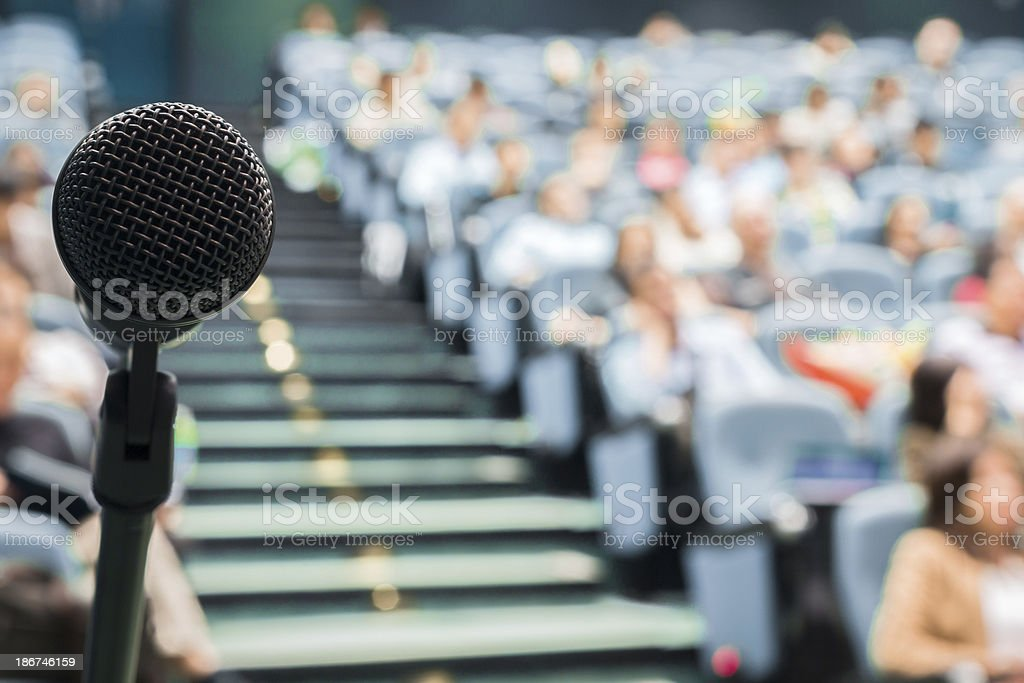 Microphone in Focus Against Blurred Audience stock photo