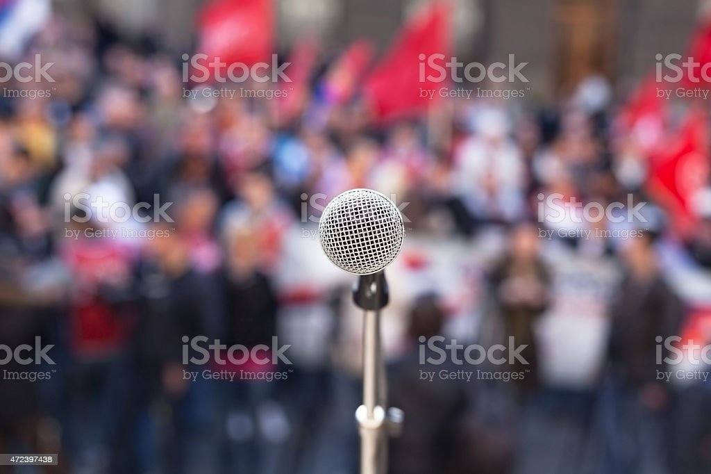 Microphone in focus against unrecognizable crowd of people stock photo