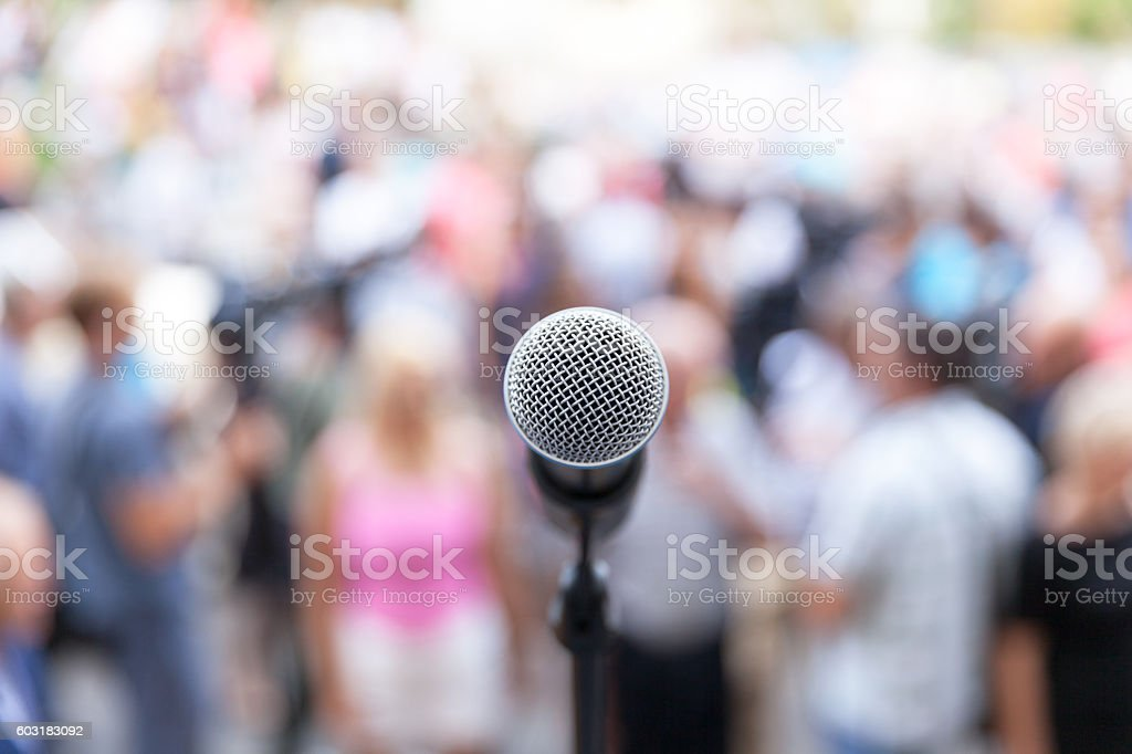 Microphone in focus against unrecognizable crowd royalty-free stock photo