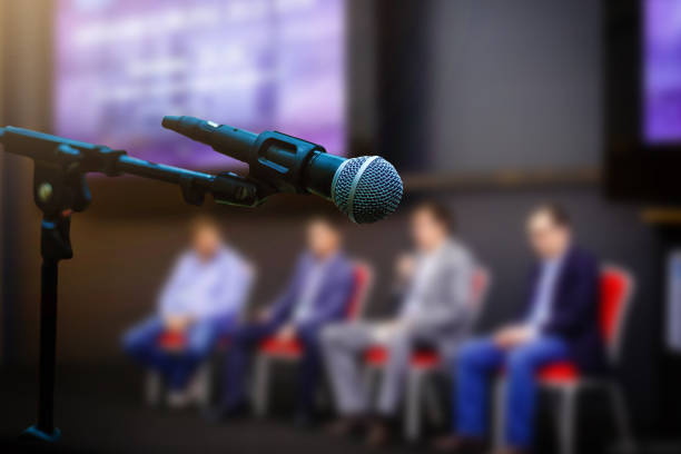 Microphone in front businesspeople blurred in conference meeting room stock photo