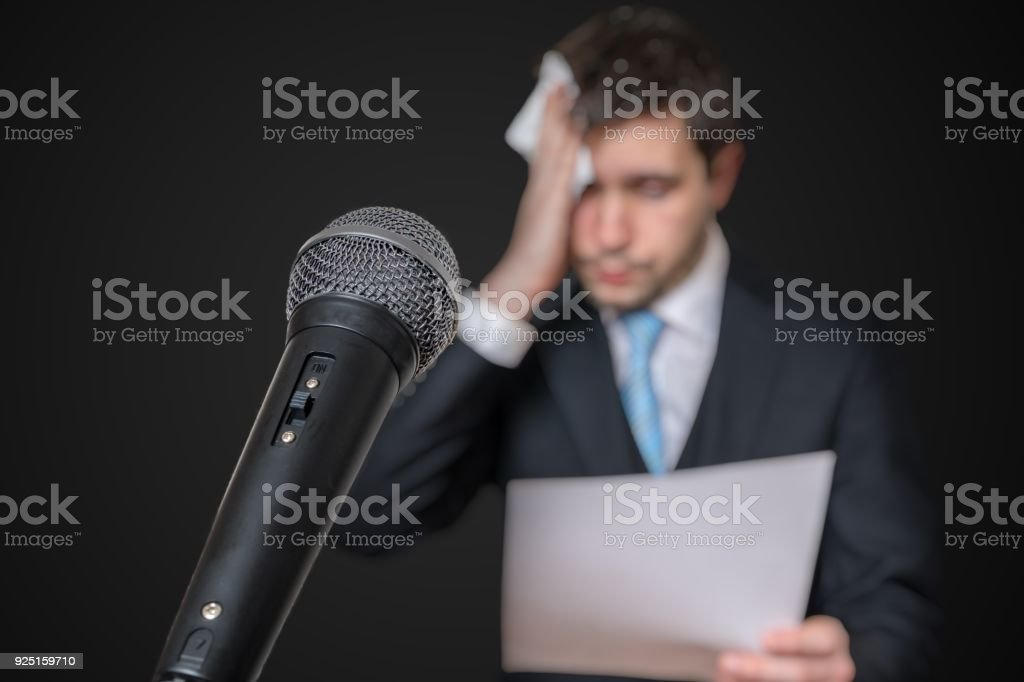 Microphone in front of a nervous man who is afraid of public speech and sweating. stock photo
