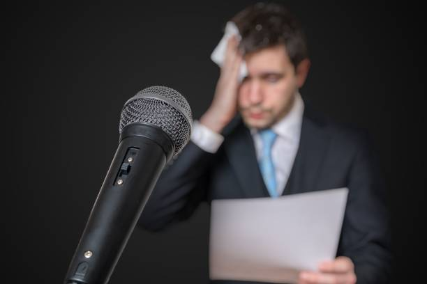 Microphone in front of a nervous man who is afraid of public speech and sweating. Microphone in front of a nervous man who is afraid of public speech and sweating. speech stock pictures, royalty-free photos & images