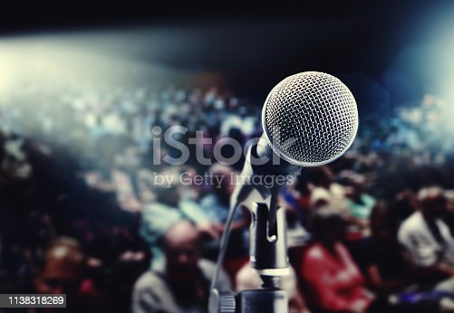 Vocal microphone waits in front of a large, unrecognizable theatre audience, lit from the rear of the theatre.