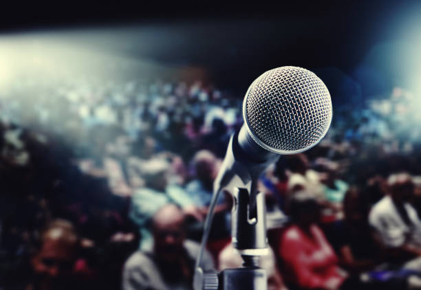 Microphone in front of large defocused theatre audience stock photo