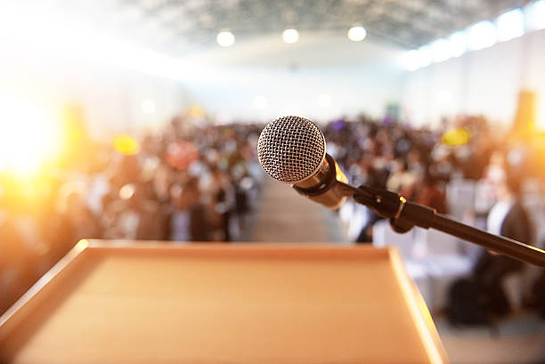 Microphone in front of podium with crowd in the background - Photo