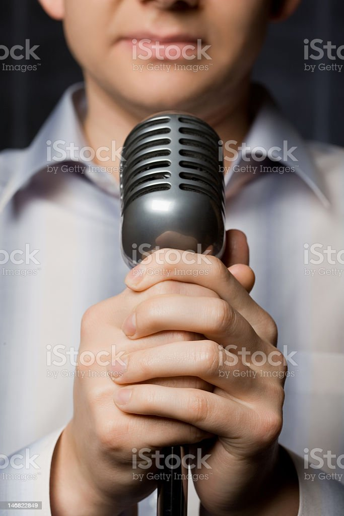 Microphone in hands of man, focus on fingers stock photo