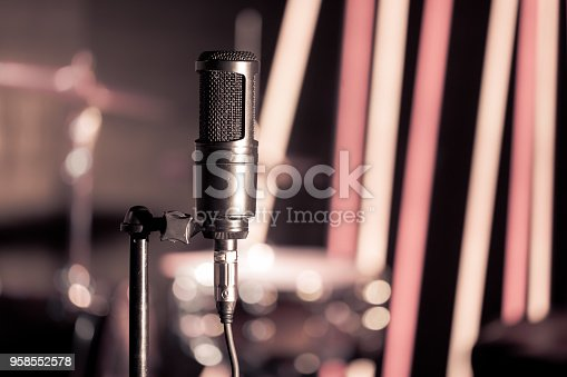 istock Microphone in recording Studio or concert hall close-up, with drum set on background out of focus. 958552578