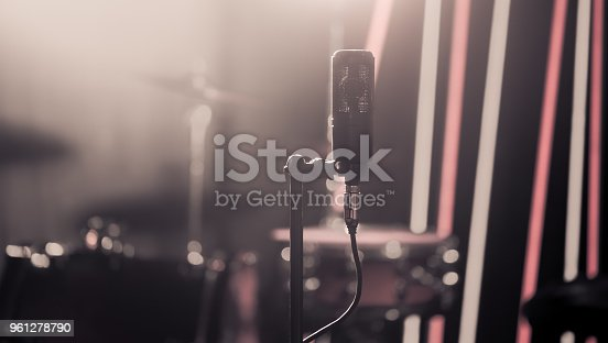 istock Microphone in recording Studio or concert hall close-up, with drum set on background out of focus. 961278790