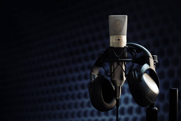 Microphone in recording studio Studio microphone and headphones on mic stand against gray background recording studio stock pictures, royalty-free photos & images