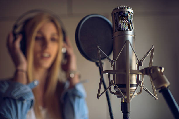 Microphone In Recording Studio With Singer The Background Stock Photo